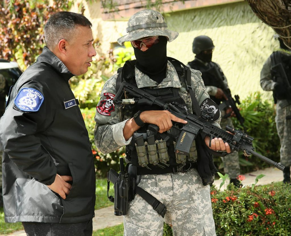 Commissioner of Police Gary Griffith, left,  briefs a Special Operations Officer at a townhouse at Regents Dr, east West Moorings, Trinidad,  where a major drug bust took place on December 4, 2018. FILE PHOTO