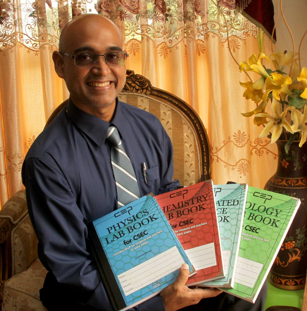 ASJA Boys' College teacher Shareek Ali with SBA lab books for science subjects which he wrote to help students. PHOTOS BY ROGER JACOB