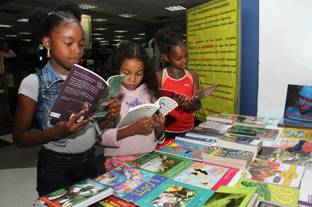 From left: Keianna Luces, Dylan Colthrust and Jasmine Alexis read story books at Bocas Lit Fest at Nalis Port-of-Spain last Wednesday. PHOTO BY AYANNA KINSALE