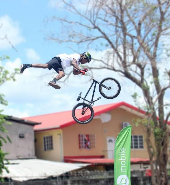 Jonathan Camacho, pro BMX rider from Ecuador, goes airborne with a trick while performing at the Chaguanas North Secondary.