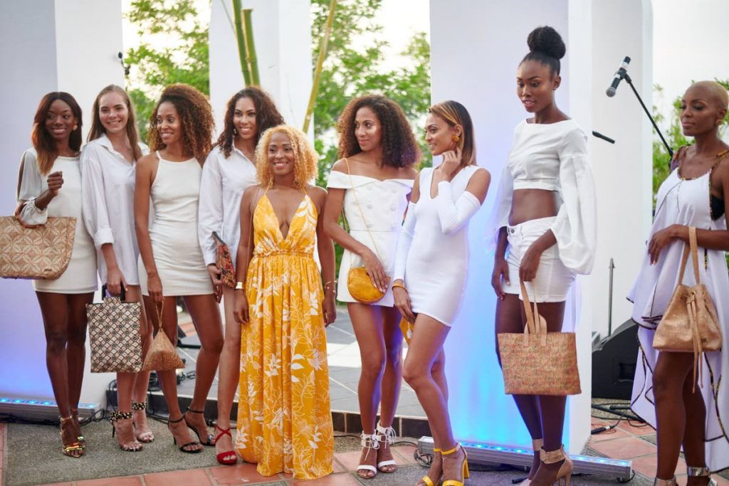 Avien Osanie(centre)poses with models wearing her handbags and earing designed by Osanie Designs at the Leve Global event hosted at Villa Being, Arnos Vale, Sunday evening. Osanie is from Mason Hall Tobago and has been designing bags using cork material for over three years.