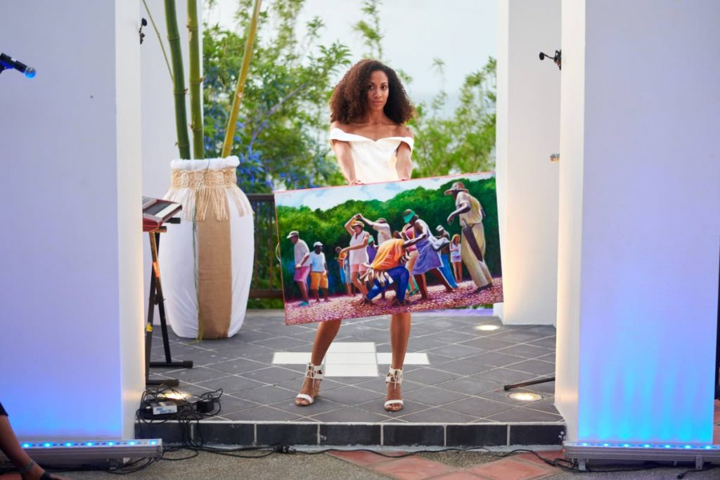 A model displays a painting by artist Jason Nedd during the fourth edition of Leve Global at Villa Being, Arnos Vale, Tobago on Sunday.   PHOTO BY LEEANDRO NORAY