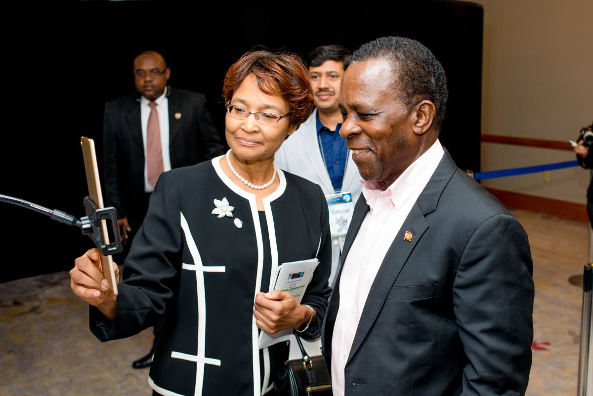 CHECK IT OUT: Caribbean Telecommunications Union (CTU) secretary general Bernadette Lewis (left) demonstrates the use of facial recognition to Prime Minister Dr Keith Mitchell during a tour of Caribbean FutureScape at the CTU 30th anniversary week of ICT-related activities held last week at the Hyatt Regency, Port of Spain.