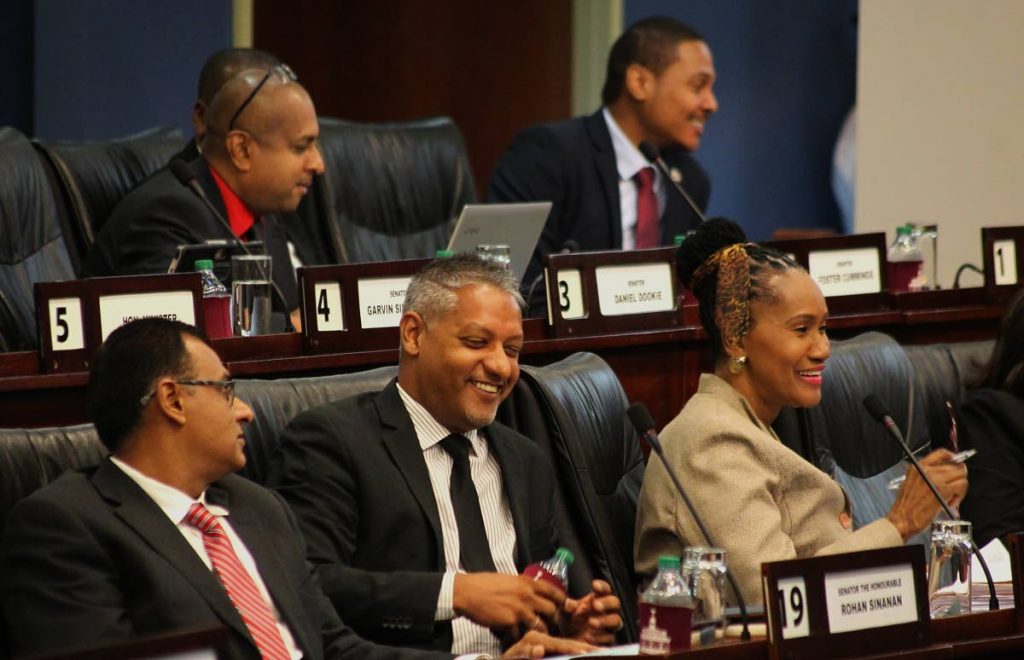 Senator Clarence Rambharat, Minister of Agriculture, Land and Fisheries, centre, and other government senators enjoy a light moment in the Senate yesterday during debate on the National Emblems of TT amendment bill.