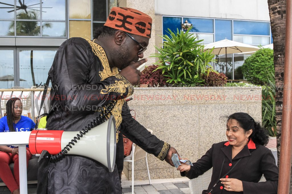 PSA president Watson Duke distributes $100 notes to all the female public servants gathered at the Hyatt Waterfront, Port of Spain. Public Servants gathered with Duke to protest workers' salaries and backpay.  Photos: Jeff K Mayers
