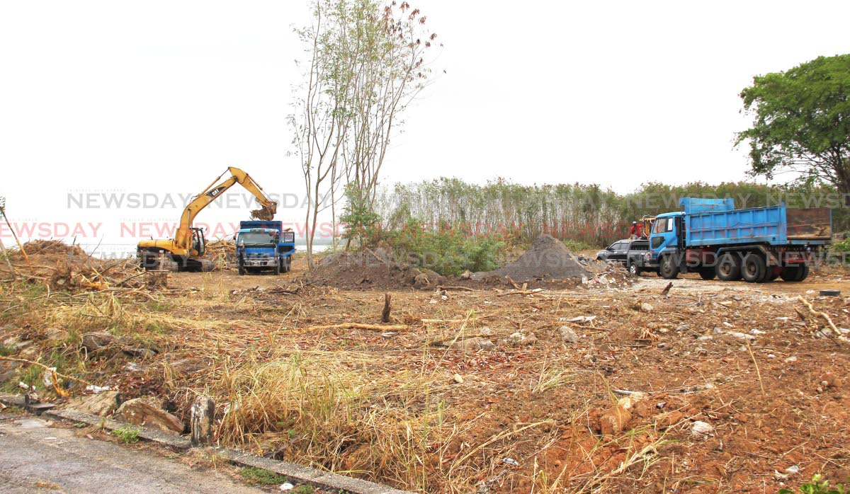 An excavator clears an area along Kings Wharf, San Fernando as part of the waterfront development project. Udecott has announced DravoSA Ltd, a firm from Madrid, Spain has been awarded the contract to reclaim 3.8 hectares of land. PHOTOS BY LINCON HOLDER