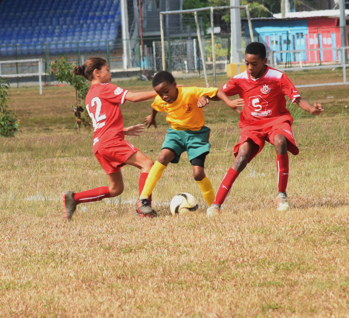 Jahseem Celestine of Trendsetter Hawks, centre, slips between Proseres' Kaitlyn Darwent, left, and Jonathan Mason in the Under 11 division of the Republic National Youth League. PHOTO BY KERWIN PIERRE