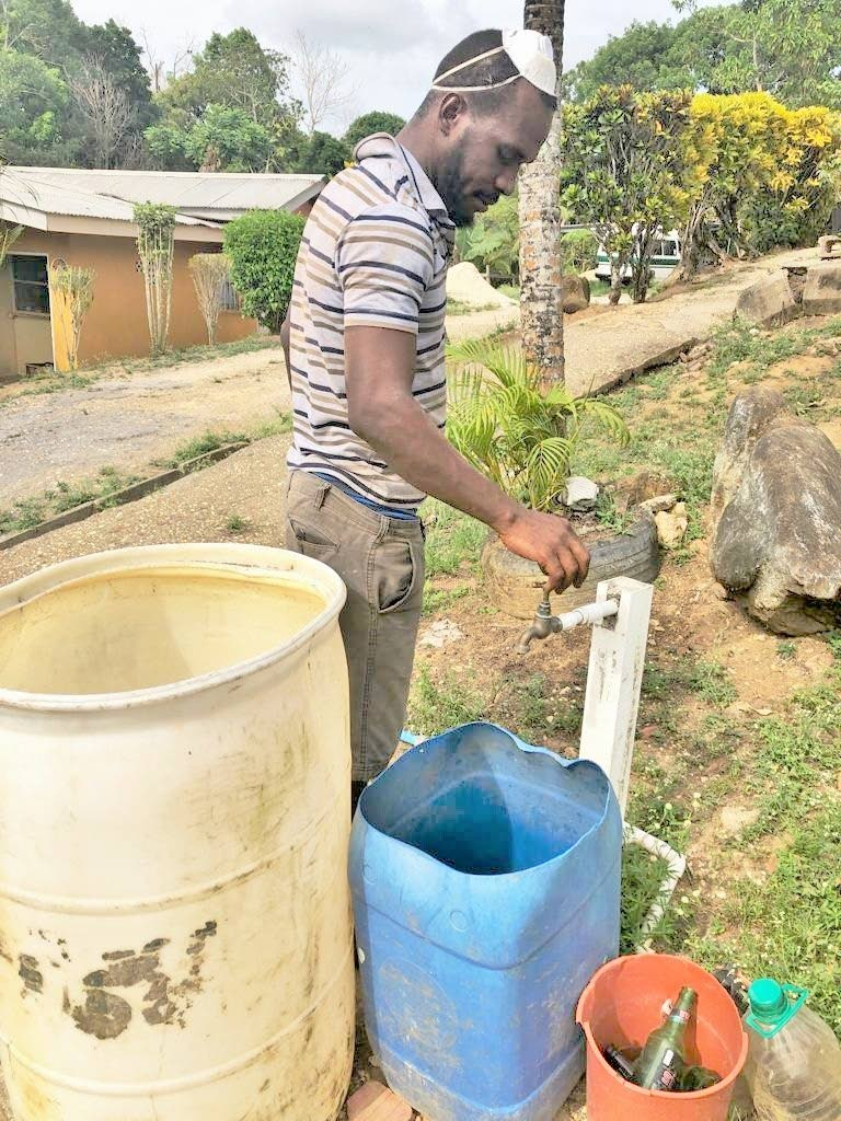 File photo: A villager opens a standpipe in Poonah Village, Williamsville to find that there is no water. PHOTO BY SEETA PERSAD