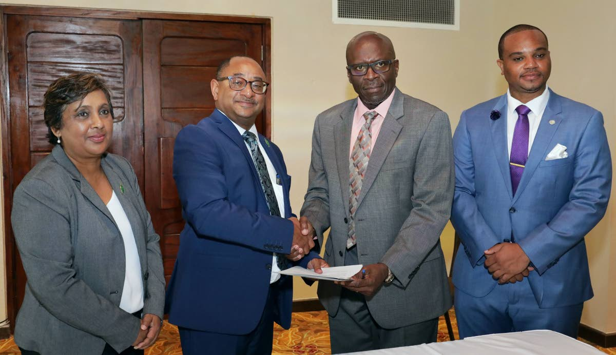 (left) Chairman of the Environmental Management Agency Nadia Gyan and (extreme right) THA Secretary of the Division of Infrastructure, Quarries and the Environment, Councillor Kwesi Des Vignes looks on as (seated left) EMA managing director Hayden Romano and THA Chief Administrator Raye Sandy  signs an MOU.