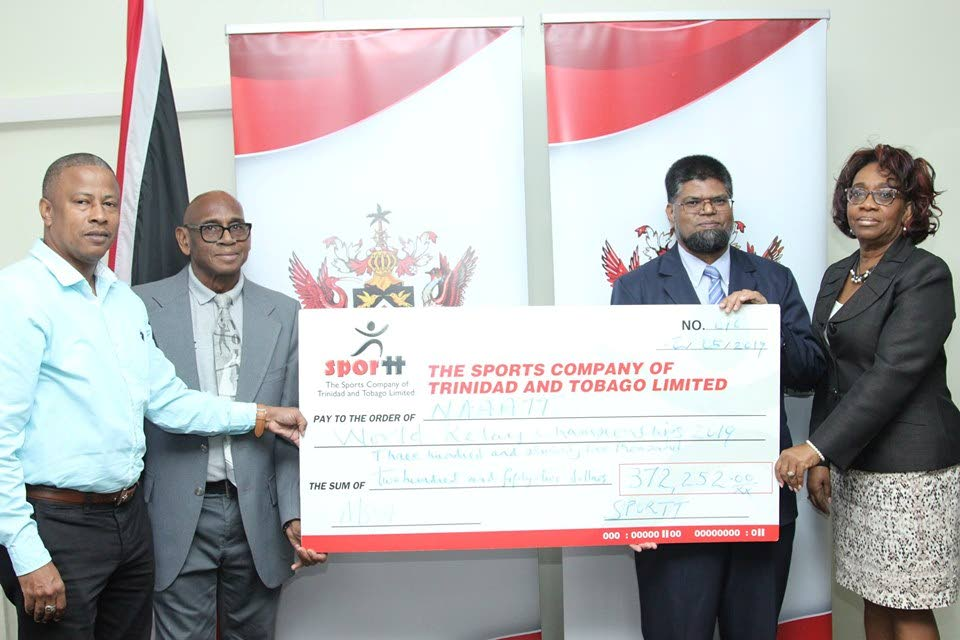 A ceremonial cheque in the amount of $372,250 is presented to NAAA general secretary Dexter Voisin, left, ahead of the IAAF World Relays in Yokohama, Japan. Also in the photo are Anthony Creed of SporTT, second left, permanent secretary at Ministry of Sport and Youth Affairs Farouk Hosein, second right, and deputy permanent secretary at the ministry Denise Arneaud.