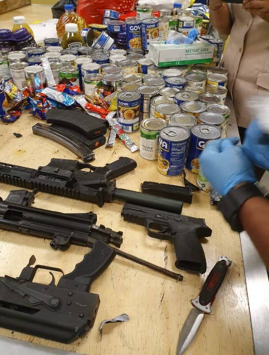 SEIZED: A Customs and Excise officer uses gloves to handle illegal firearms found hidden in a barrel intercepted yesterday at the Port in Port of Spain.