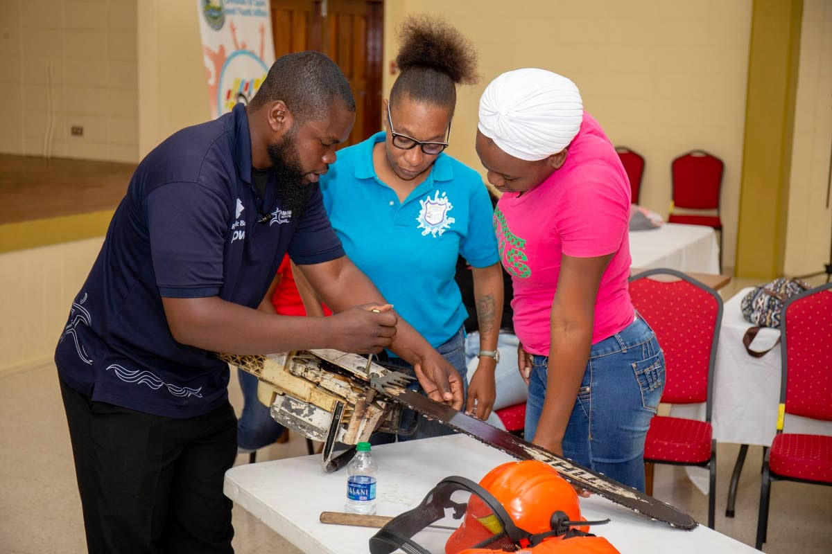 These women learn how to operate a chainsaw at a disaster preparedness and management workshop last week. PHOTO BY DSYA THA