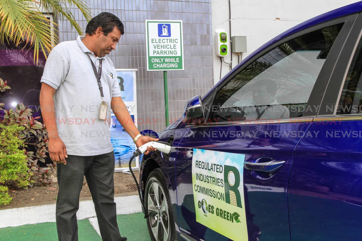 Regulated Industries Commission (RIC) office courier, Daniel Ramsepaul demonstrates how to charge the company's electric vehicle outside the RIC's Wrightson Road, Port of Spain office. Members of the public charge their vehicles at the charging station. PHOTO BY JEFF K MAYERS