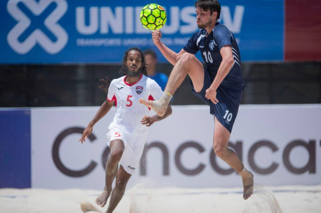 TT's Chad Appoo (left) watches as Turks and Caicos' Alex Bryan intercepts the ball during Monday's match.TT will take on Panama today in a quater-final match up.