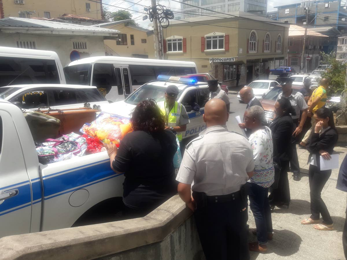 Magistrate, prosecutor and police inspect a vendor's goods outside San Fernando High Court yesterday