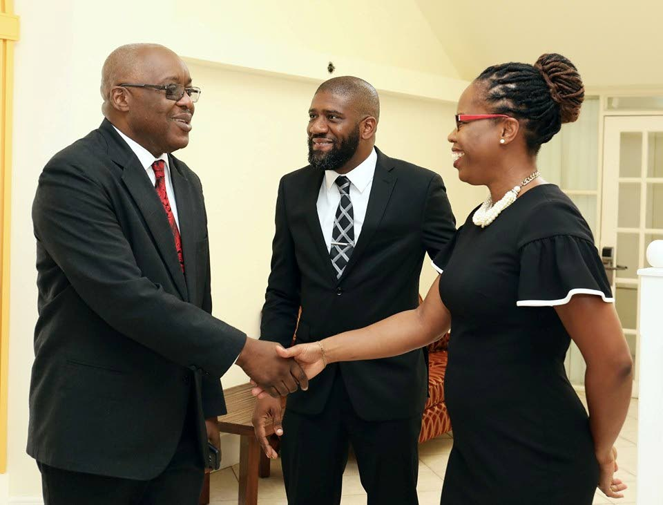 Chief Sec Kelvin Charles greets Director, Compliance and Outreach of the Financial Intelligence Unit, Avelon Perry as FIU member Kevin Radix looks on.