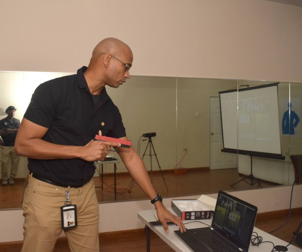 Dirk Barnes demonstrates the imarksman sport simulator used as part of training for all his security personnel. Photo by Vidya Thurab