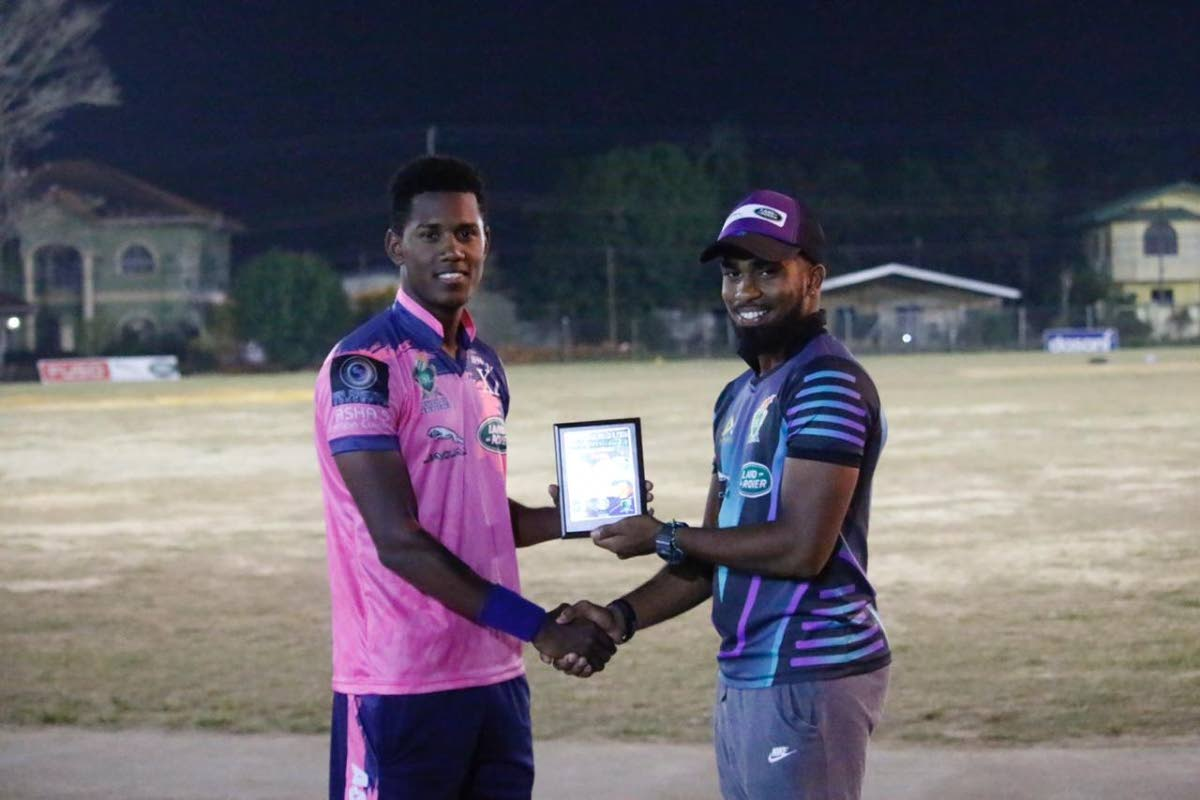 Akeal Hosein (left) collecting his Man of the Match award from fellow TT player Bryan Charles.