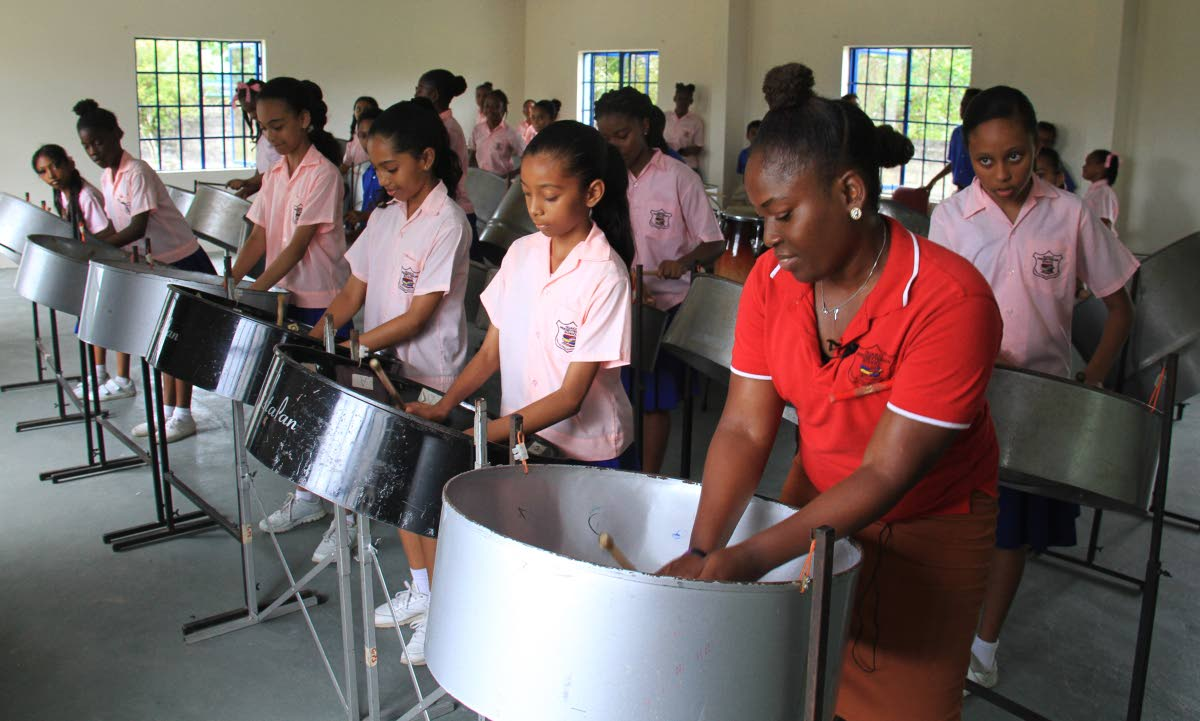 Anna Noel, artistic director of the Guaico Presbyterian Steel Orchestra, practises with her  students last Wednesday. PHOTO BY AYANNA KINSALE.