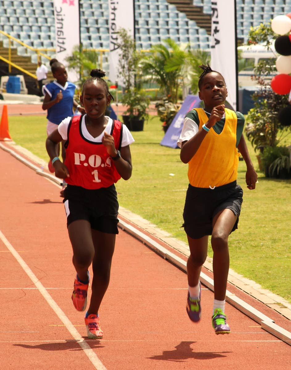 This pair of runners go head-to-head to the finish line in the girls open 1,500 metres yesterday.