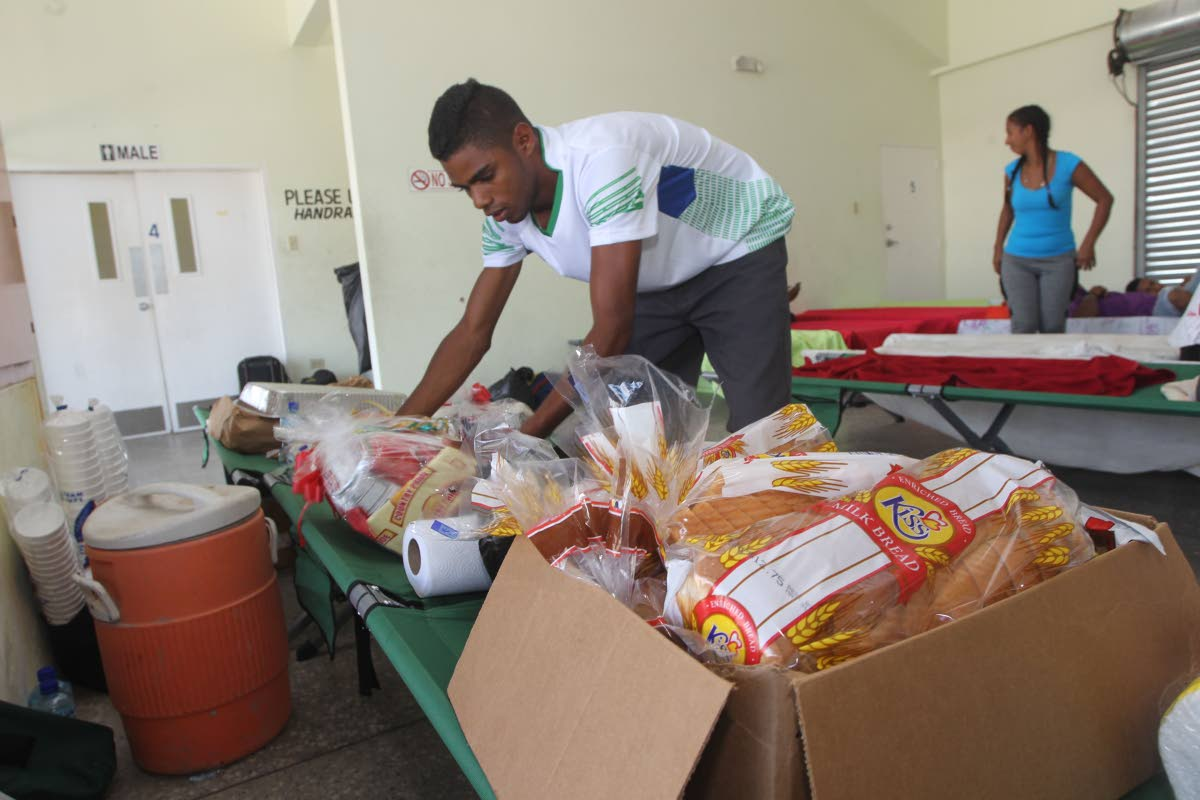 A man examines the food items dropped off at Irwin Park Sporting Complex on Thursday where medical care was being given to the Venezuelans who had arrived illegally on Wednesday. PHOTO BY LINCOLN HOLDER