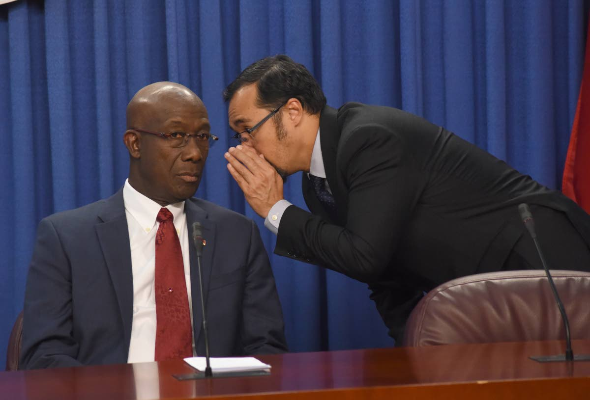 National Security Minister Stuart Young has a private conversation with the Prime Minister at yesterday's post-Cabinet news conference at the Diplomatic Centre in St Ann's.