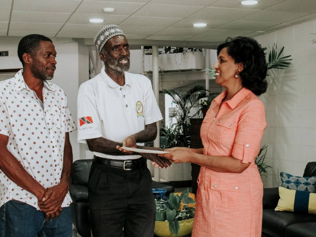 Karen Nunez-Tesheira, right, presents a cheque to Ruthvin Charles, middle, and Dexter Harris.