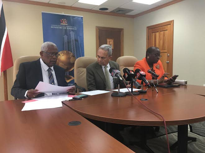 Finance Minister Colm Imbert looks over at Education Minister Anthony Garcia at a press conference on the government's school construction programme. At right is Planning Minister Camille Robinson Regis