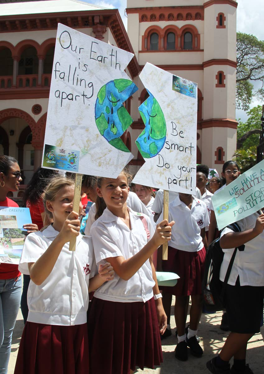 "Gabriella Chaves and Zoe Camacho, both of St Bernadette's Prep School in St Ann's, hold up their unique poster illustrating the need to protect ""Mother Earth"" at the Laudato Si' Generation Climate Change march, at Jackson Square, opposited the Archbishop's residence in St Clair, yesterday."