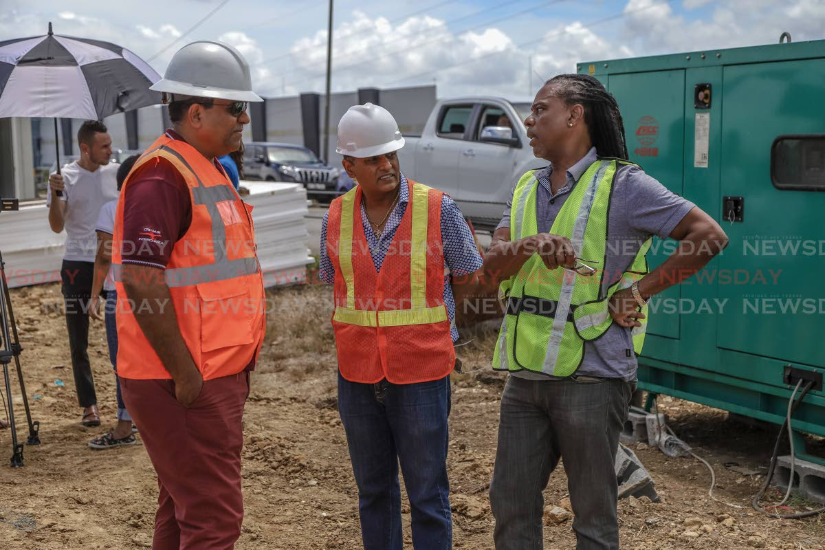 From left: Navin Ramsingh, director of the Highways Division, Minister of Works and Transport Rohan Sinanan, and PURE programme director Hayden Phillip in talks during a demonstration of the Government's new culvert replacement method on the Solomon Hochoy Highway, Freeport, Sunday. JEFF K MAYERS