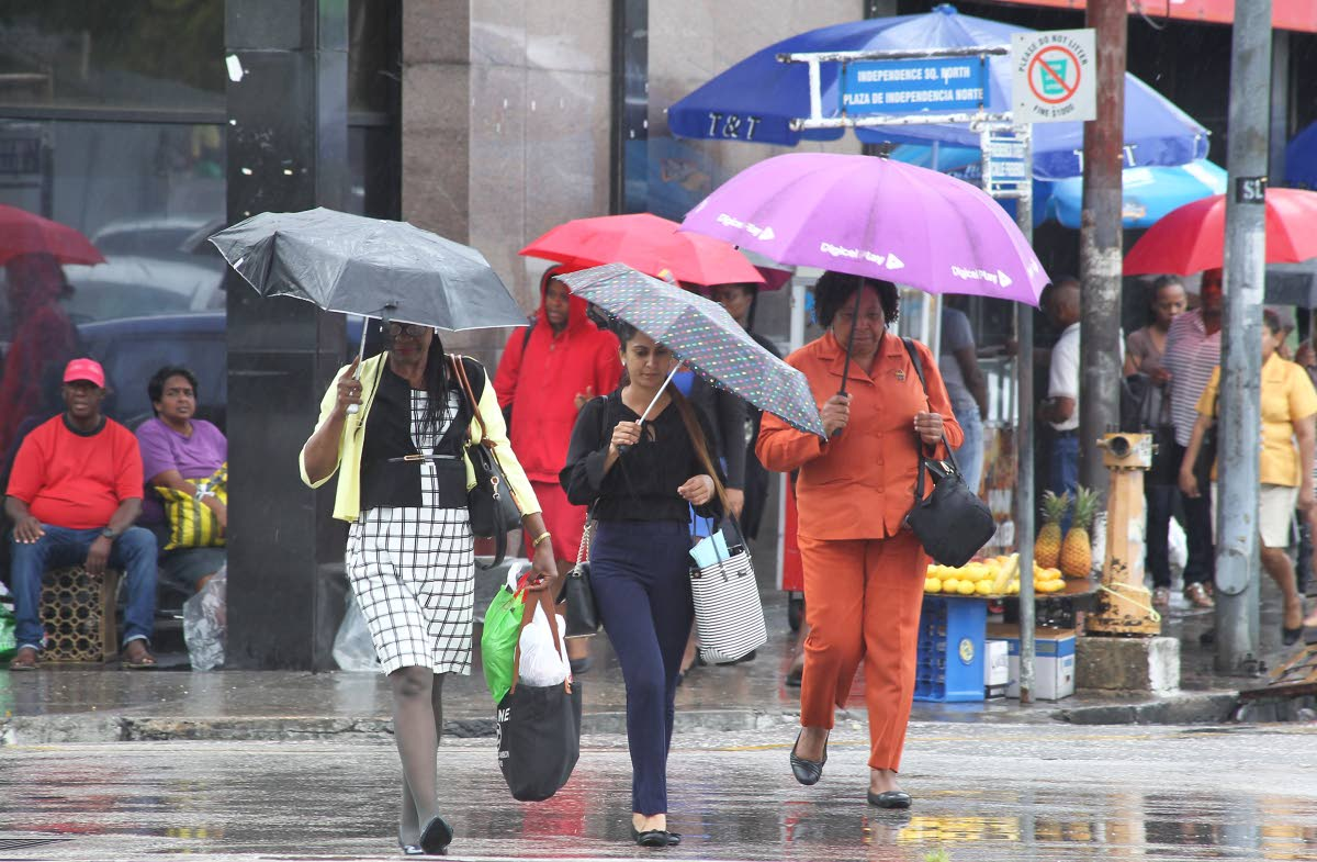 File photo: Pedestrians with their trusty umbrellas walk through rain along Independence Square in Port of Spain.