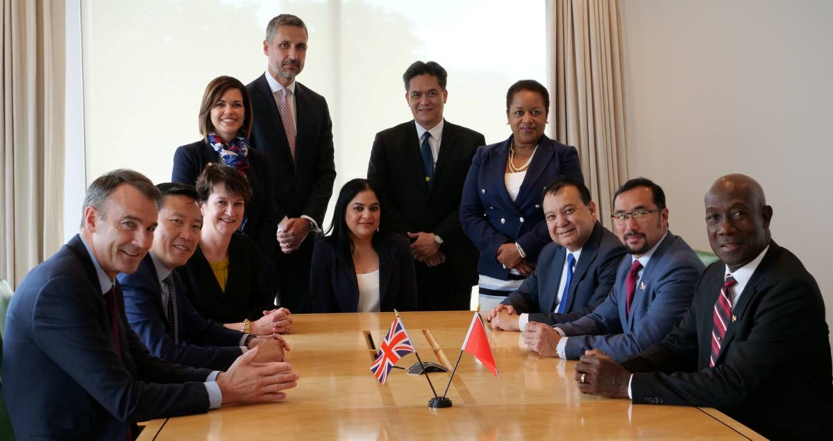 PM Dr Keith Rowley, right, leads his team at negotiations in London yesterday with a BP team led by chief executive upstream Bernard Looney, left. PHOTO COURTESY OPM