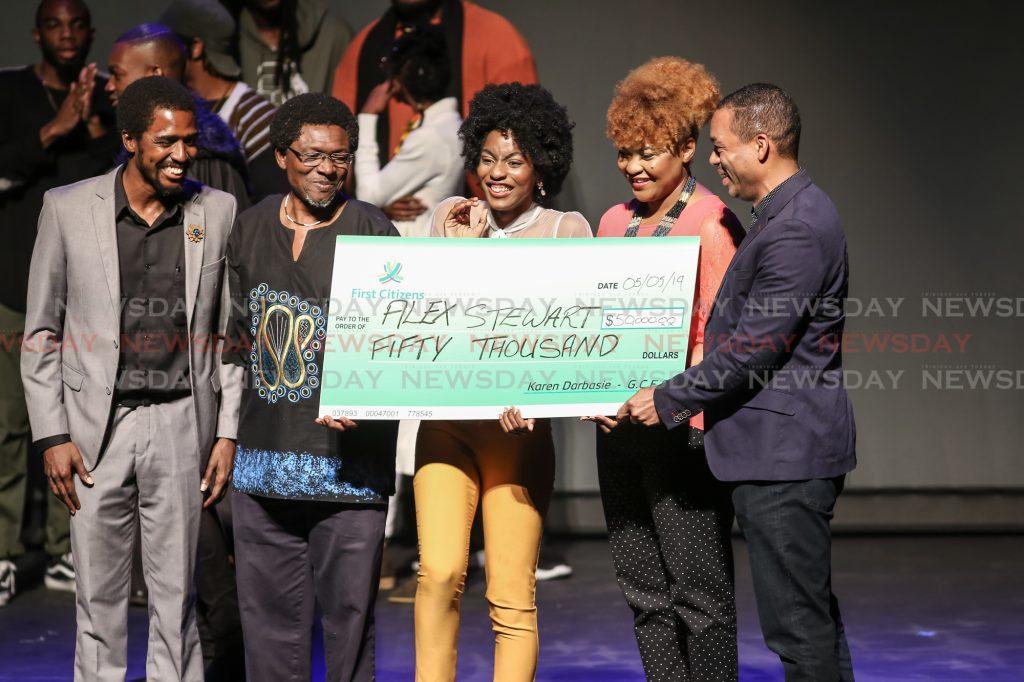 Winner, Alexandra Stewart (centre)receives a cheque  from First Citizens Bank Deputy CEO Jason Julien (right).  Phot by Jeff K. Mayers