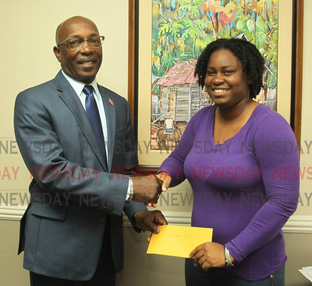 Makeisha Simon, receives a cheque donation from Newman George, Chairman of HDC, in his personnal capacity to help assist her in fund her dream of becoming a doctor, Office of the Chairman, Housing Development Corporation, Port of Spain. Tuesday, June 4, 2019. PHOTO BY ROGER JACOB.