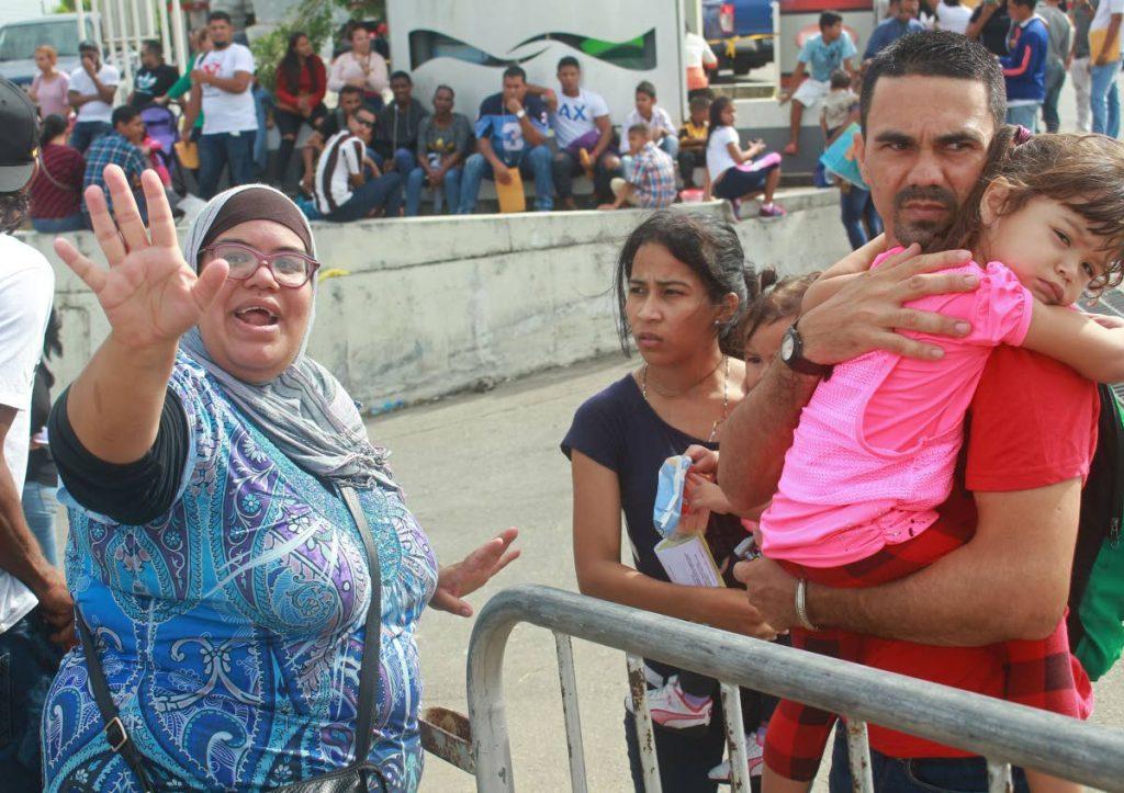 File photo: Venezuelan Martha Tovar, left, helps her compatriots get registered at Achievor's Banquet Hall, Duncan Village, San Fernando.