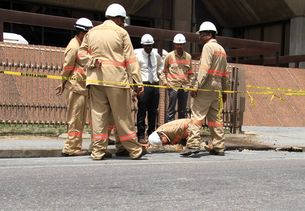 T&TEC general manager Kelvin Ramsook takes a look at the damage done to the road after there was an explosion at the corner of Duke and Abercromby Street last Friday.