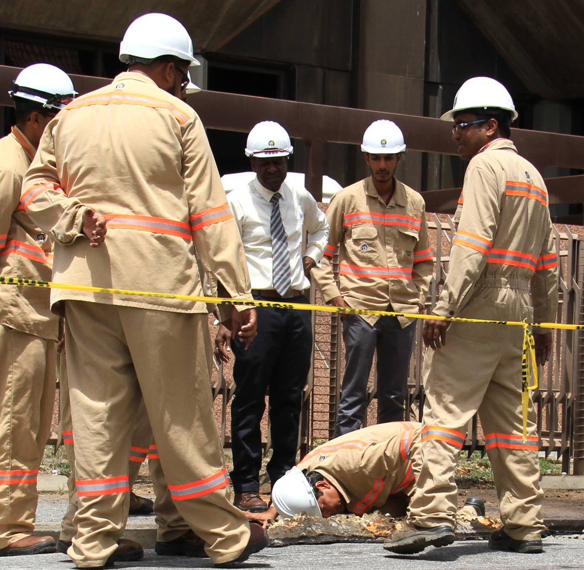 HAVING A LOOK SEE: In this file photo T&TEC general manager Kelvin Ramsook (kneeling) examines buried cables under the pavement outside  the Hall of Justice which was the scene of the explosion. PHOTO BY AYANNA KINSALE