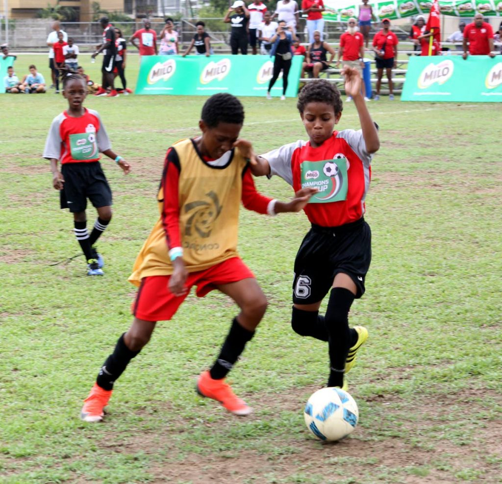 Cox Coaching School's Vaughn Clement,left, and Ginga FC's Aidan Byer battle for the ball, during play in the Milo Championship Cup 2019, at the UWI-Spec Grounds, St Augustine, yesterday.