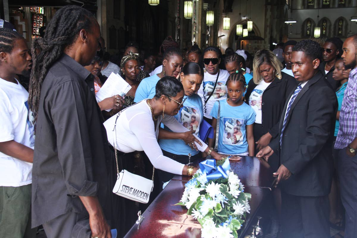 SORROW: Kimette Johnson, left, touches the casket of her son Kadeem during his funeral yesterday at the Holy Trinity Cathedral in Port of Spain. PHOTO BY AYANNA KINSALE