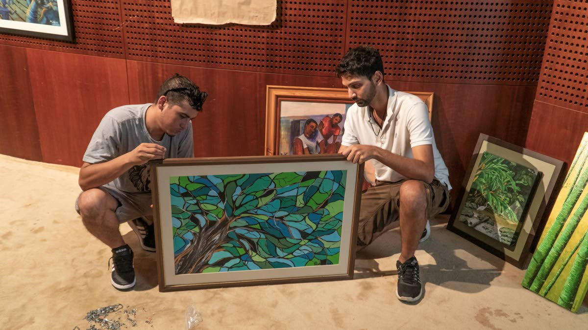 Visualart Galleries directors Jonathon Mora, left, and Joshua Persad, get Nicole Tang's painting Looking Up From Under The Tree ready to mount up for the exhibition.