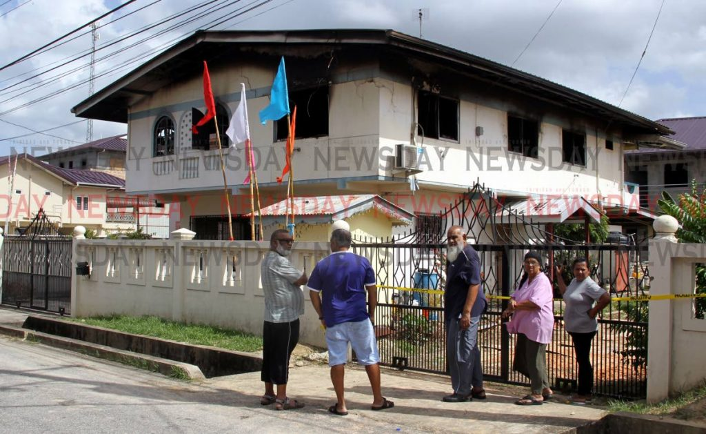 Neighbours gather outside the Samroo Street home of the Singh family, who died in a fire there on Wednesday morning. Photo by Roger Jacob.