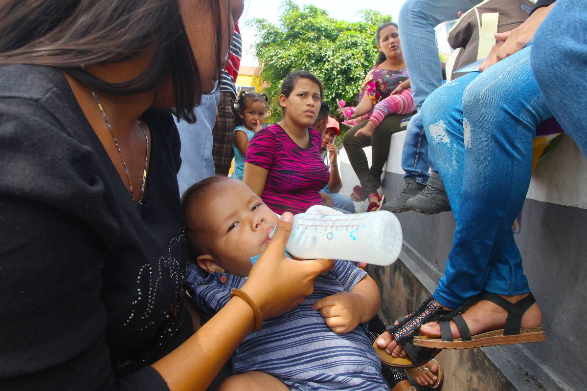 ROADSIDE FEED: Baby boy Haiseell Caraballo drinks from a bottle as he and his mother joined hundreds of Venezuelans in line waiting to be registered yesterday at the Achievors Banquet Hall in San Fernando. PHOTO BY LINCOLN HOLDER