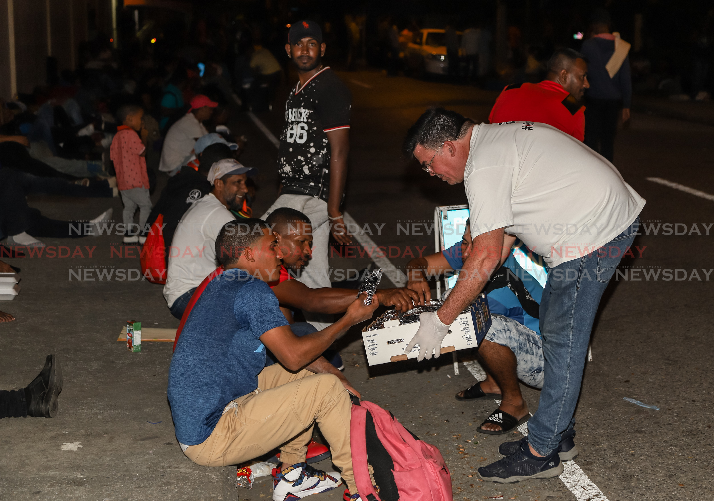 Artist Peter Sheppard distributing food to Venezuelans outside the Queen's Park Oval registration centre last night.  Photos: Jeff K Mayers