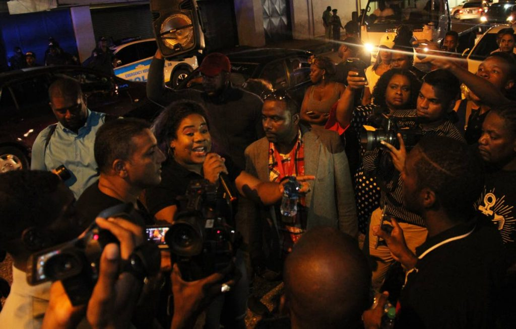 Kia Hosein addresses supporters during a protest outside Queen's Park Oval, Port of Spain on June 13 under the watch of  plainclothes officers. PHOTO BY AYANNA KINSALE