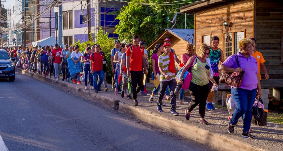 Scores of Venezuelans walk through Scarborough to Port Mall on the final day of registration last Friday. PHOTO BY DAVID REID
