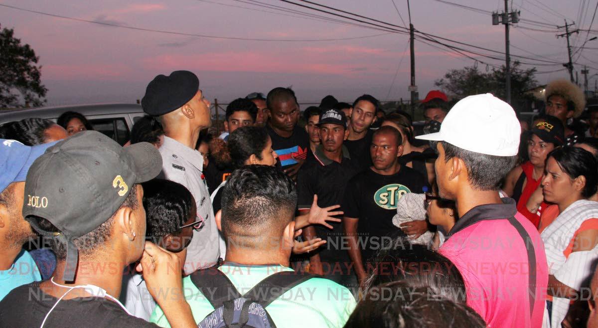 A policeman addresses Venezuelans as they wait to register at Achievors Hall, Duncan Village, San Fernando late Friday evening. PHOTO BY VASHTI SINGH
