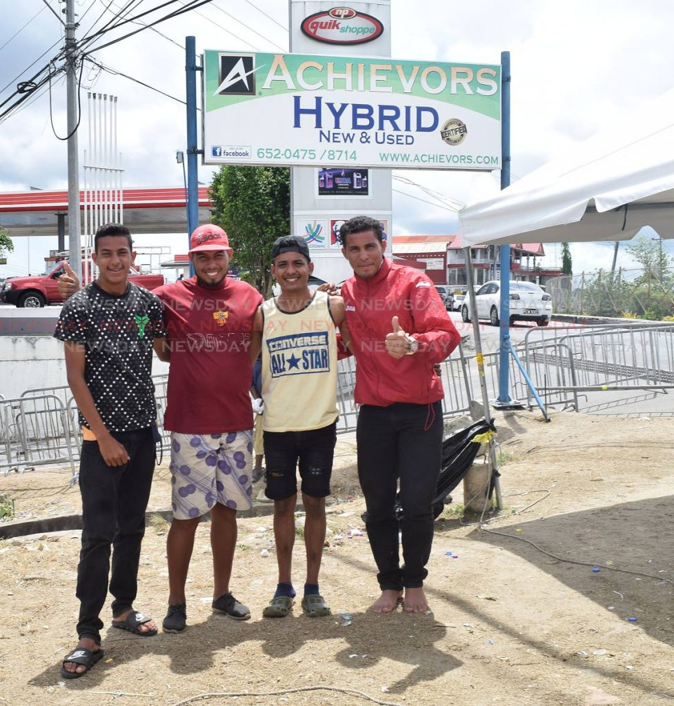 File photo: Venezuelans Diego Salazar, Valentin Osuna, Albert Astudillo and Eduard Pulvett are all smiles as they await their transport at Achievors Hall, Duncan Village ,San Fernando after completing the registration process last month. PHOTO BY VIDYA THURAB