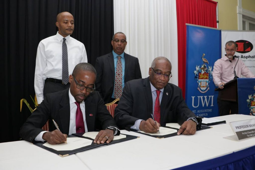SIGNED: CEO of Lake Asphalt TT Ltd Roger Wiggins, left, and The UWI St Augustine campus principal Prof Brian Copeland sign the licence agreement while Dr Richard Fairman, standing at left, Stephen  Mc Clashie and Julian Henry, far right, look on. PHOTO COURTESY THE UWI