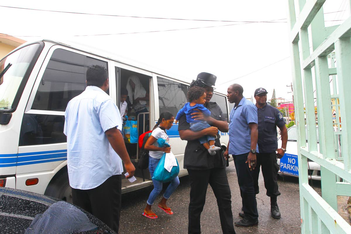 OUT OF TIME: Several Venezuelans, including a baby in a policewoman's arms, were taken to the Immigration Department in San Fernando yesterday after they were found to have illegally entered the country.