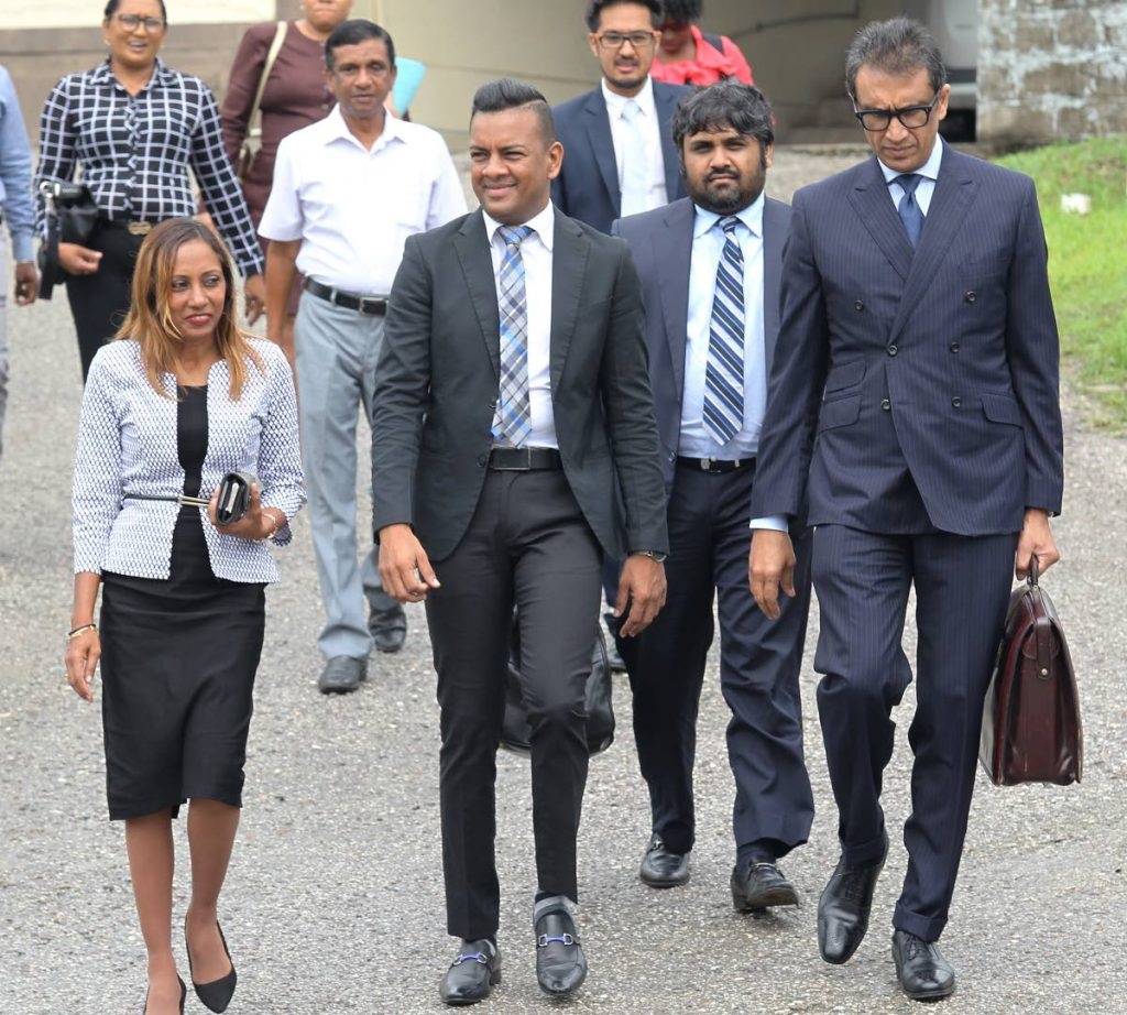 Chairman of the Mayaro/Rio Claro Regional Corporation, Glen Ram, second from left, leaves the Rio Claro Magistrates' Court on Tuesday. PHOTO BY LINCOLN HOLDER